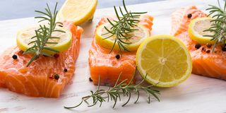 Raw salmon on wooden board with herbs Royalty Free Stock Photography