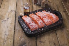 Raw salmon pieces on wooden board with herbs, salt and spices.  Royalty Free Stock Photo
