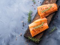 Raw salmon on wooden board with herbs Stock Photos