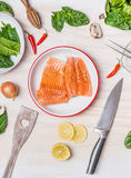 Raw salmon portion in bowl on white kitchen table background with cooking ingredients, spoon and knife Royalty Free Stock Photos