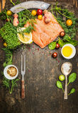 Raw salmon preparation for cooking on rustic wooden background with fresh ingredients , fork and spoon, top view Royalty Free Stock Photos