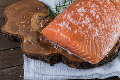 Raw salmon with salt and pepper. Raw salmon with salt and rosemary on rustic background Stock Photo