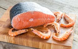 Raw salmon and shrimps on the wooden board Royalty Free Stock Photos