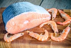 Raw salmon and shrimps on the wooden board Royalty Free Stock Images