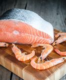 Raw salmon and shrimps on the wooden board Stock Images