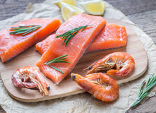 Raw salmon with shrimps on the wooden board. Slices of raw salmon with shrimps on the wooden board Royalty Free Stock Photos