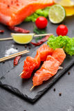 Raw salmon skewers on a stone plate Royalty Free Stock Image