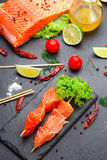 Raw salmon skewers on a stone plate. tomatoes, lime and lettuce Stock Photos