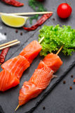 Raw salmon skewers on a stone plate. Stock Photos
