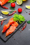 Raw salmon skewers on a stone plate. Royalty Free Stock Photos