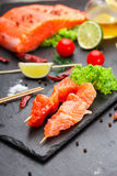 Raw salmon skewers on a stone plate. Royalty Free Stock Photography