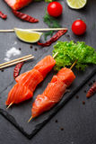 Raw salmon skewers on a stone plate. Royalty Free Stock Image