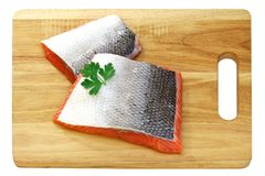 Raw salmon with skin on wooden cutting board. Isolated on a white background Royalty Free Stock Photo