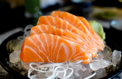 Raw salmon slice or salmon sashimi. Raw salmon slice or salmon sashimi in Japanese style fresh serve on ice with fresh wasabi photo in  indoor low lighting Stock Photography