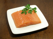 Raw salmon steak. With parsley on a small plate stock photo