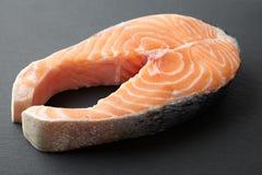 Raw salmon steak, appetite fish. On a dark background Stock Photos
