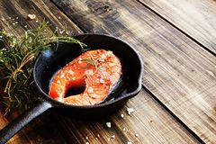 Raw salmon steak on  cast-iron pan with rosemary Stock Photos