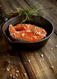 Raw salmon steak on  cast-iron pan with rosemary Stock Photography