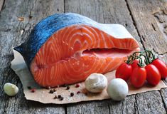 Raw salmon steak with cherry tomato, mushroom, onions, dill, garlic, lemon and olive oil Stock Images