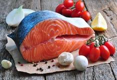 Raw salmon steak with cherry tomato, mushroom, onions, dill, garlic, lemon and olive oil Royalty Free Stock Photo