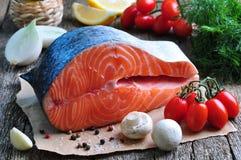 Raw salmon steak with cherry tomato, mushroom, onions, dill, garlic, lemon and olive oil Stock Photo
