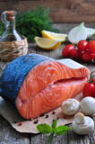 Raw salmon steak with cherry tomato, mushroom, onions, dill, garlic, lemon and olive oil Stock Photos