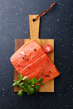 Raw salmon steak on cutting board. Cooking Royalty Free Stock Images