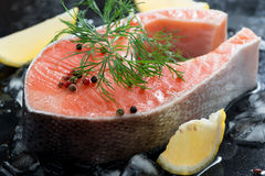 Raw salmon steak with dill and lemon on ice, close-up. Horizontal Stock Image