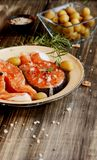 Raw salmon steak on an enamel plate with rosemary Stock Images