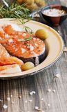 Raw salmon steak on an enamel plate with rosemary Stock Image