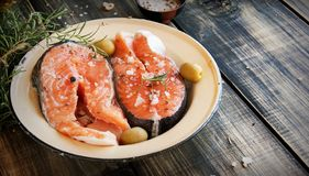 Raw salmon steak on an enamel plate with rosemary Royalty Free Stock Images