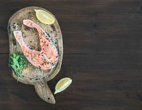 Raw salmon steak with fresh herbs, lemon and spices on rustic wo Stock Image