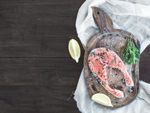 Raw salmon steak with fresh herbs, lemon and spices on rustic wo Royalty Free Stock Image