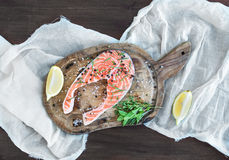 Raw salmon steak with fresh herbs, lemon and spices on rustic wo Royalty Free Stock Photos