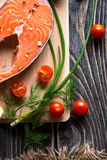 Raw salmon steak. Fresh raw salmon steak on wooden cutting board with salt, tomatoes and herbs Stock Photos