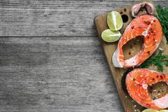 Raw salmon steak with herb, lemon and peppercorns on wooden cutting board. healthy and diet food. top view. With copy space Royalty Free Stock Photos
