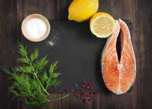 Raw salmon steak with herbs and lemon. Raw salmon steak with herbs and lemon on black board Stock Photos