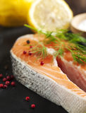 Raw salmon steak with herbs and lemon. Royalty Free Stock Image