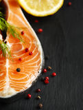 Raw salmon steak with herbs and lemon. Stock Photos