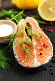 Raw salmon steak with herbs and lemon. Raw salmon steak with herbs and lemon on black board Royalty Free Stock Image
