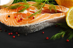 Raw salmon steak with herbs and lemon. Raw salmon steak with herbs and lemon on black board Stock Image