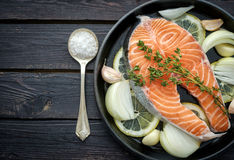 Raw salmon steak with herbs, onion, garlic and salt on a vintage. Pan on wooden rustic background. Top view Stock Photo