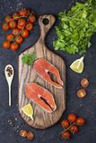 Raw salmon steak with herbs, parsley and lemon. On a dark background Royalty Free Stock Photos