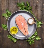 Raw salmon steak with herbs, parsley, olive oil and salt on a vintage pan wooden rustic background top view close up. Raw salmon steak with herbs, parsley, olive Stock Photos