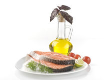 Raw salmon steak with herbs, vegetables. And olive oil over white background Stock Images