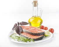Raw salmon steak with herbs, vegetables. And olive oil over white background Stock Photos