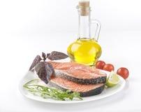 Raw salmon steak with herbs, vegetables stock photos