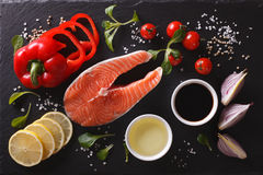 Raw salmon steak and ingredients on a black board. Horizontal to Stock Images