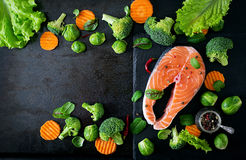 Raw salmon steak and ingredients for cooking. Raw salmon steak and ingredients for cooking on a dark background in a rustic style. Top view Stock Photos