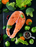 Raw salmon steak and ingredients for cooking. Raw salmon steak and ingredients for cooking on a dark background in a rustic style. Top view Royalty Free Stock Image
